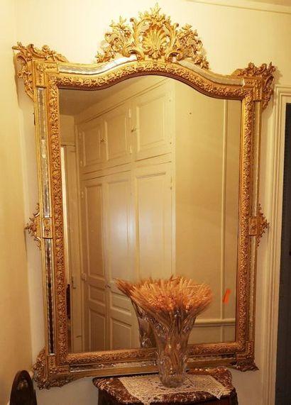 Grand miroir à parecloses gravés de frises de pirouettes, à fronton en coquille...