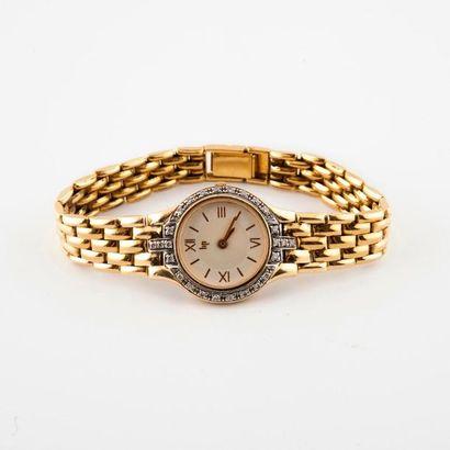 LIP  Montre bracelet de dame en or jaune (750)  Boîtier rond.  Lunette ornée de...