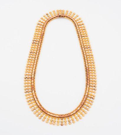 Collier draperie en or jaune (750) à motifs de fleurs stylisées.  Fermoir cliquet....