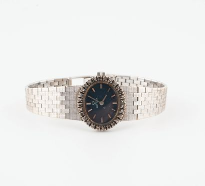 OMEGA Montre bracelet de dame en or gris (750).  Boîtier ovale, lunette ornée de...