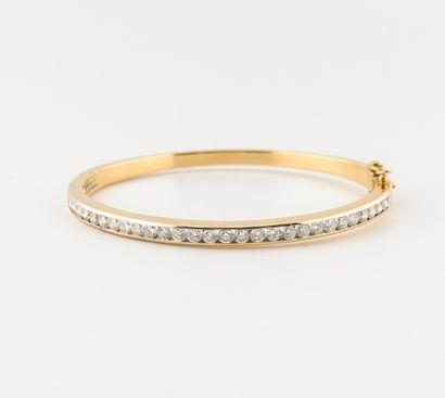 Bracelet jonc ouvrant en or jaune (750) ornée d'une ligne de diamants de taille...