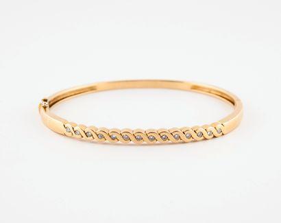 Bracelet ovale rigide, ouvrant, en or jaune (750) orné de treize petits diamants...