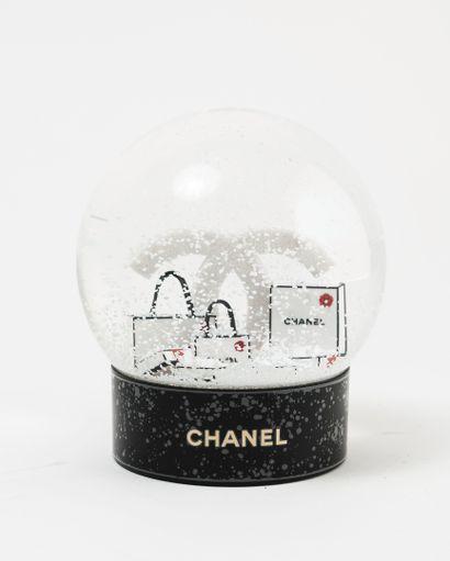 CHANEL Boule à neige à décor du sigle et sacs de la maison.  H. : 11,5 cm.  Avec...