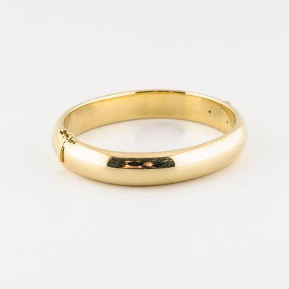 Bracelet jonc ouvrant en or jaune (585) creux.  Fermoir cliquet avec huit de sécurité....