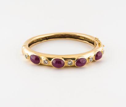 Bracelet jonc ouvrant en or jaune (750) orné de quatre cabochons de racine de rubis...