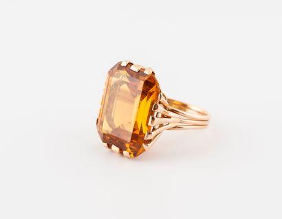 Bague en filins d'or jaune (750) ornée d'un saphir jaune-orangé synthétique de taille...