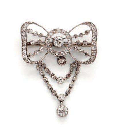 Élégante broche noeud ajouré en or gris (750) et platine (850), ornée de diamants...