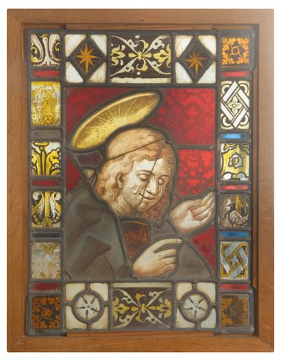 Stained glass window depicting a holy figure, probably Saint John.  In polychrome...