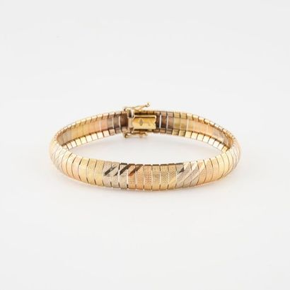 Bracelet ruban en or jaune (750) de trois tons, à décor amati de bandes obliques....