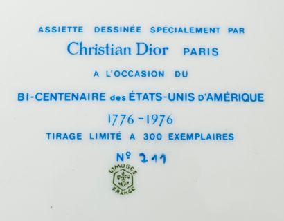 CHRISTIAN DIOR PARIS Assiette en porcelaine blanche à décor en bleu et rouge d'une...