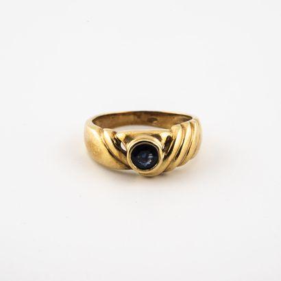 Bague en or jaune (750) ornée d'un petit saphir rond facetté en serti clos, à épaulement...