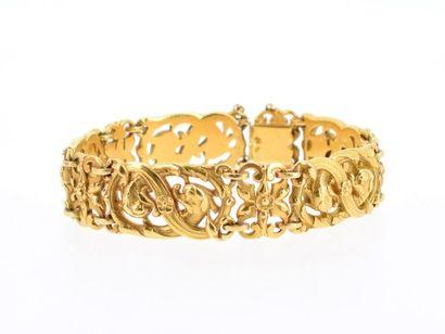Bracelet souple en or jaune 18k (750 millièmes) à motifs de chimères dans un décor...