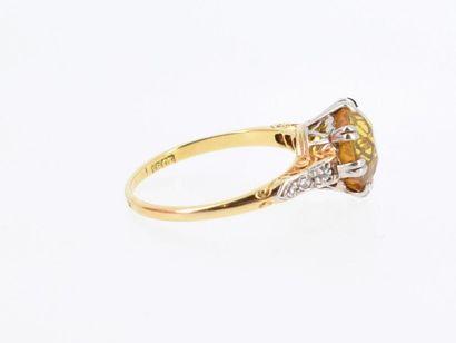 Charmante bague deux tons d'or 18k (750 millièmes) ornée d'un saphir jaune rond...
