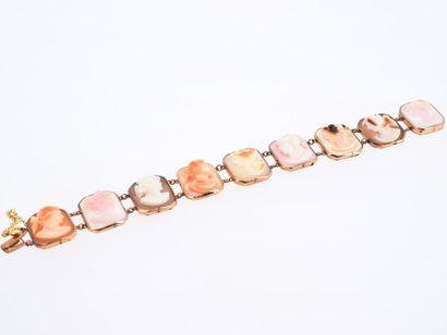 Bracelet en métal doré présentant une suite de profils à l'Antique en camée de coquillages....