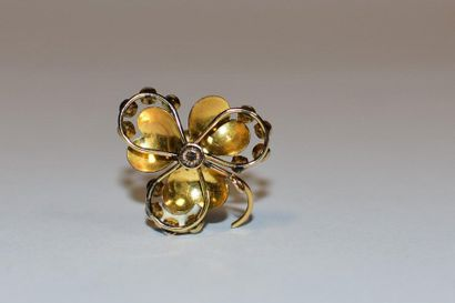 Metal brooch forming a flower set with white imitation stones.  Gross weight of...