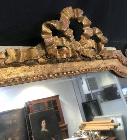 Gilded wood mirror decorated with friezes and garlands of flowers, knot-shaped pediment....
