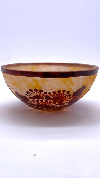 Multilayer glass bowl decorated with brown flowers and leaves on a marbled orange...
