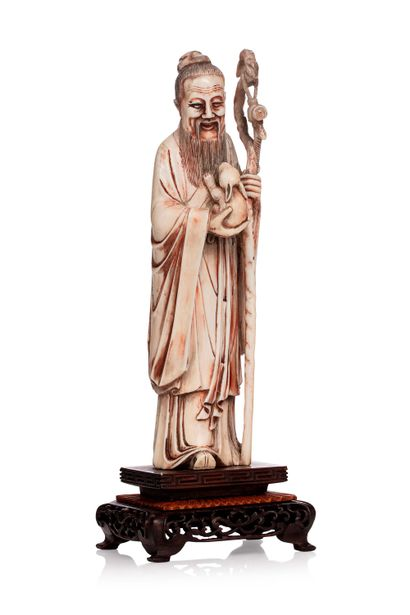 CHINE, vers 1900 Statuette d'immortel en ivoire* sculpté tenant un lapin et son baton...