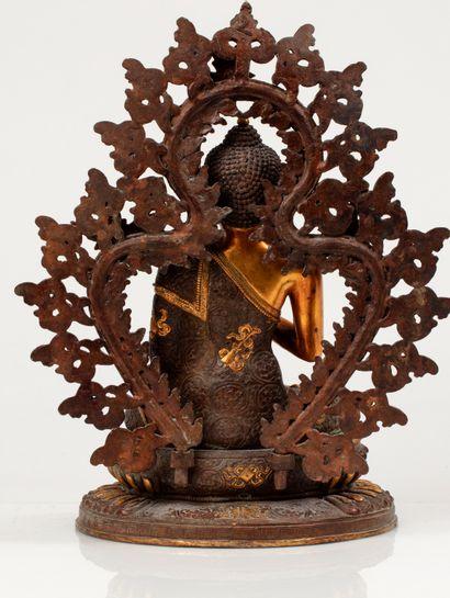 *TIBET, XXe siècle Figure de bouddha en bronze doré La divinité représentée assis...