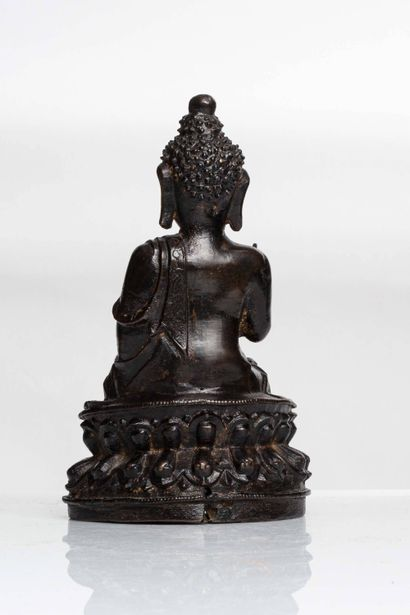 CHINE, Dynastie Ming Bouddha en bronze à patine brune représenté assis sur un socle...