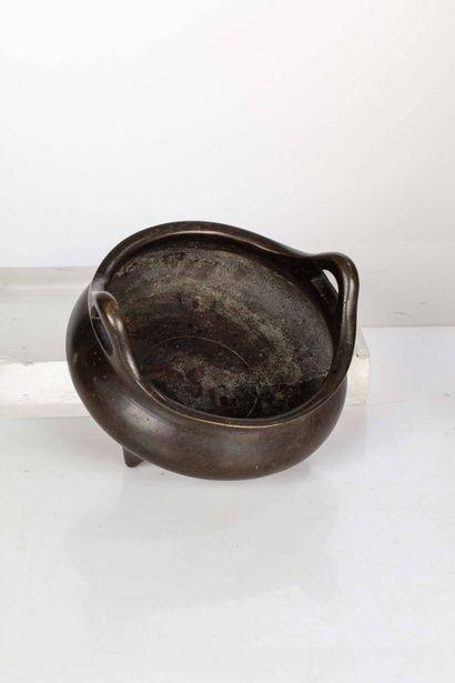 CHINE, XVIIe siècle Brûle parfum circulaire en bronze tripode, de forme bombée à...