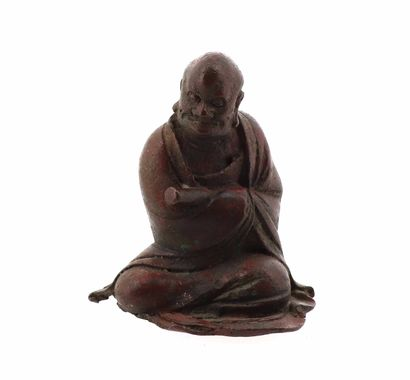 CHINE, XVIIe siècle Statuette en bronze Représentant un Luohan assis, portant un...