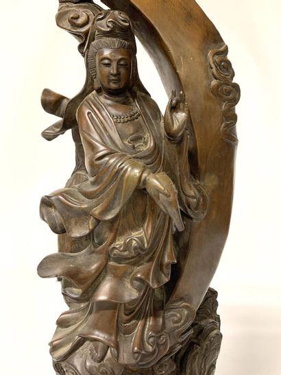 CHINE, vers 1900 Guanyin en bois sculpté Représentée debout sur un rocher, tenant...