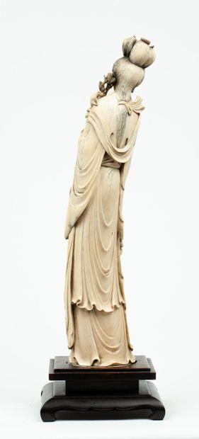 CHINE, vers 1900 Défense en ivoire* sculpté figurant une élégante Représentée vêtue...