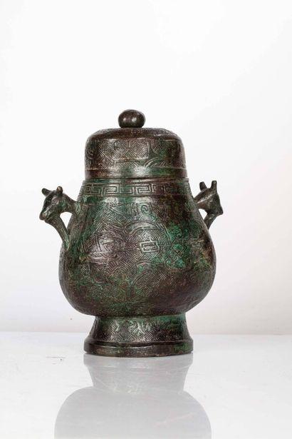 CHINE, Dynastie Ming Vase couvert en bronze, You Il présente un décor de masques...