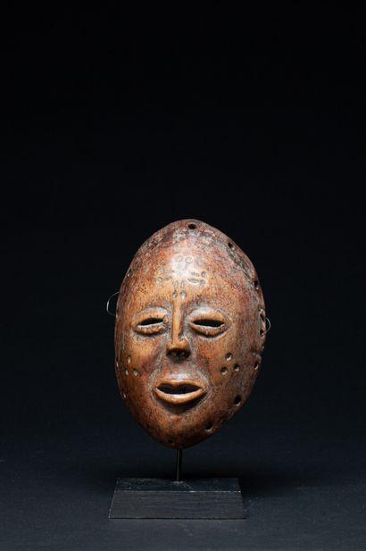 Masque de danse sculpté d'un visage à l'expression...