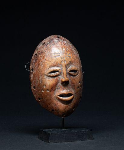 Masque de danse sculpté d'un visage à l'expression lunaire, les joues et le front...