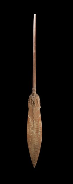 Ceremonial paddle carved on each face with...