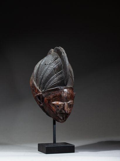 Masque guèlèdé sculpté d'un visage juvénile à l'expression joviale, la coiffe agencée...