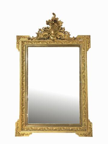 Miroir de forme rectangulaire inscrit dans un encadrement en bois sculpté et doré,...