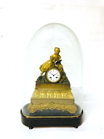 Clock in ormolu and patinated bronze decorated...