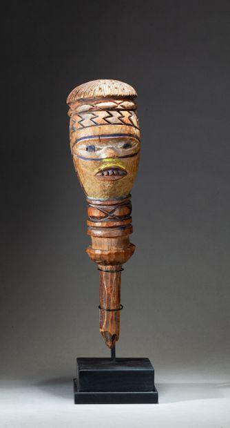 Marotte cultuelle  présentant une tête stylisée, le front orné d'un bandeau de motifs...