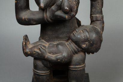 Maternité  assise présentant un de ses seins...