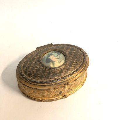 Petite boîte ovale en métal doré avec, au...