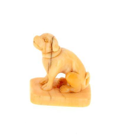 *JAPON, Période Edo Netsuke en ivoire* représentant un chien sur un socle rectangulaire...