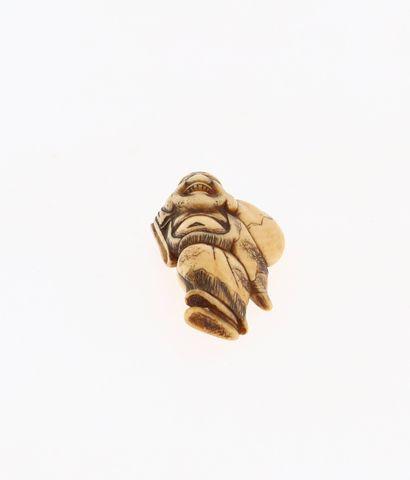 *JAPON, XVIIIe siècle Netsuke en ivoire* représentant un Hotei avec son sac de richesses...