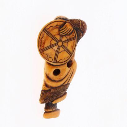 *JAPON, XVIIIe siècle Netsuke en ivoire* à patine brune représentant un homme retenant...