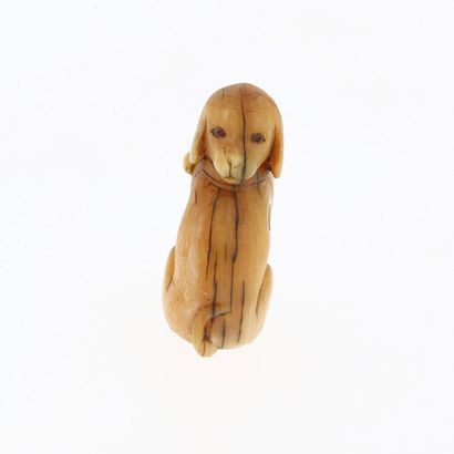 *JAPON, XVIIIe siècle Netsuke en ivoire* représentant un chien assis. Les yeux en...