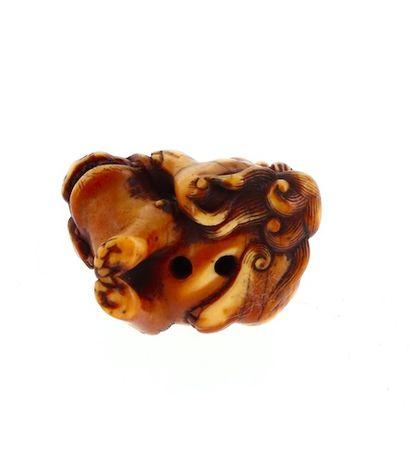 *JAPON, Époque Edo Netsuke en ivoire* à patine brune figurant Rakan assis sur un...