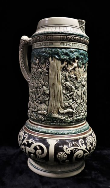 Large ceramic beer jug with abundant decoration in relief depicting a battle scene...