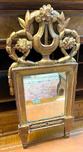Miroir en bois sculpté et doré à fronton...