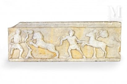 Part of a white marble frieze carved in bas-relief depicting men dressed in tunics...