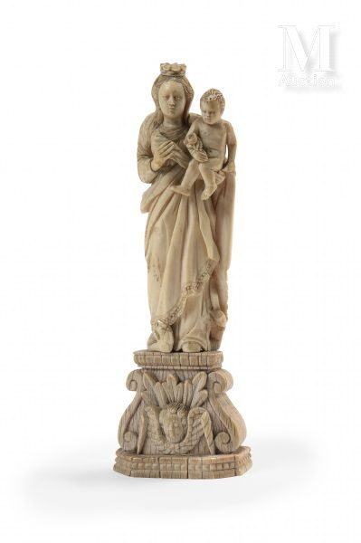 Virgin and Child in carved ivory, presented standing, dressed in drapery, carrying...