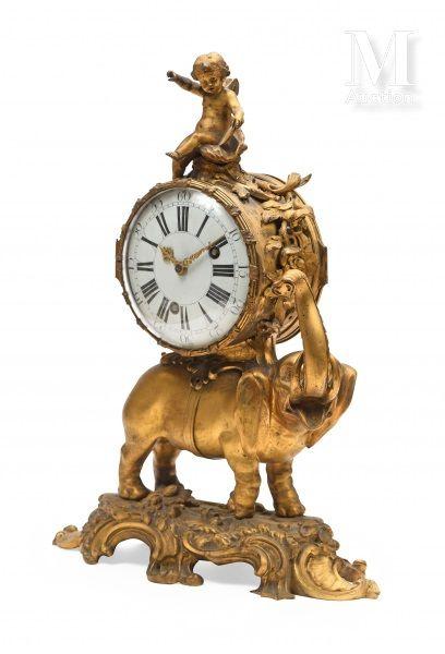 Pendule à l'éléphant, trompe levée, en bronze ciselé et doré sur un tertre rocaille....