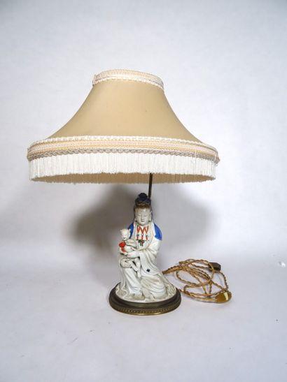 CHINE, XXe siècle Guanyin en porcelaine polychrome  Représentée tenant un enfant...