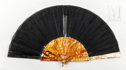 Nacre teintée orange, vers 1900-1910 Éventail plié, la feuille en gaze noire richement...